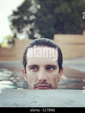Mann im pool Stockbild