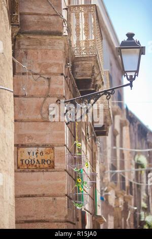 Taranto, Apulien, Italien - Eine alte Straßenlaterne an einer Hausfassade festgesetzt Stockbild