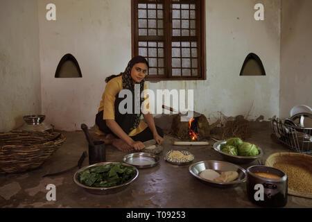 Ländliche Frau Kochen auf Brennholz in Küche mit Geschirr und Gemüse auf dem Boden. Stockbild