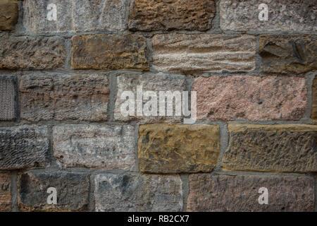 Alte Mauer eines historischen Gebäudes mit verschiedenen farbigen Steinen Stockbild