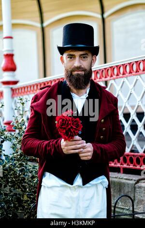 Regency gekleidet Mann hält einen Strauß roter Rosen Stockbild