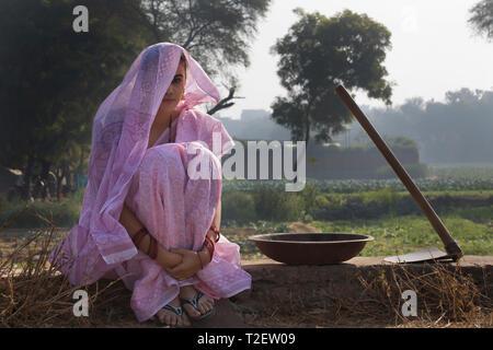 Frau Bauer oder Dorf Frau sitzt in der Nähe von Landwirtschaft Feld mit einem Spaten und Eisen Gold Pan durch Ihre Seite mit den Kopf bedeckt mit Sari. Stockbild