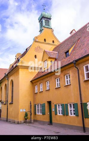 Fuggerei, Augsburg, Bayern, Deutschland - St. Markus Kirche als Von der Herrengasse aus gesehen. Stockbild