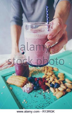 Mittelteil von einem Mann mit einem violetten Smoothie Stockbild