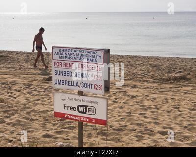 Informationen Zeichen, eine Sonnenliege und Sonnenschirm zu mieten om den Strand im Ferienort Ayia Napa Zypern, WiFi kostenlos von der Gemeinde angeboten Stockbild