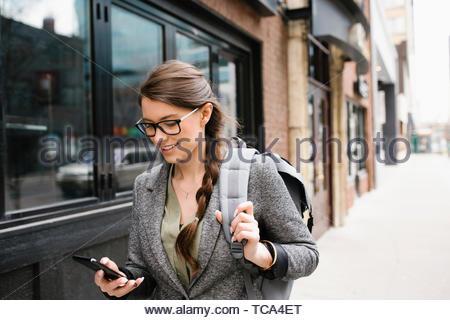 Geschäftsfrau mit Rucksack mit Smart Phone auf städtischen Bürgersteig Stockbild