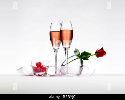 Champagner, eine rote Rose, Band und Pralinen. Stockbild