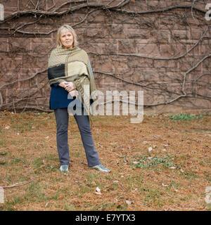 Senior Frau gegen die Wand stehen bedeckt in blattlosen Efeu Stockbild