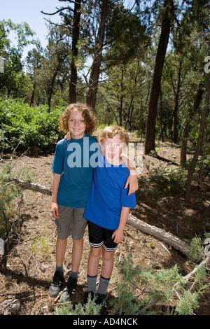 Zwei jungen stehen zusammen in einem Wald Stockbild