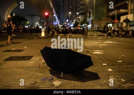 Ein Regenschirm zur Festlegung im Boden nach Polizei und Demonstranten aneinandergeraten sind. Die Demonstranten mit den Hong Kong Polizei am Ende der bürgerlichen Menschenrechte vor März. Hong Kong Demonstranten versammelten für ein weiteres Wochenende der Proteste gegen die umstrittene Auslieferung Rechnung und mit einer wachsenden Liste von Beschwerden, die der Aufrechterhaltung des Drucks auf Chief Executive Carrie Lam. Stockbild