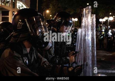 Die bereitschaftspolizei Kontrollen sein Handy während der Ausbildung beim Reinigen der Connaught Road. Die Demonstranten mit den Hong Kong Polizei am Ende der bürgerlichen Menschenrechte März Sai Ying Pun, Hongkong, China, am Sonntag, den 21. Juli 2019. Hong Kong Demonstranten versammelten für ein weiteres Wochenende der Proteste gegen die umstrittene Auslieferung Rechnung und mit einer wachsenden Liste von Beschwerden, die der Aufrechterhaltung des Drucks auf Chief Executive Carrie Lam. Stockbild