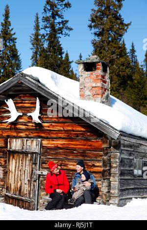 Familie sitzt im Freien im Winter Stockbild