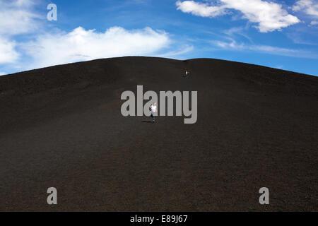 Jungen und Mädchen läuft am Krater des Mondes Stockbild