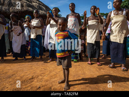 Junge mit einem Superman T-shirt Vor dan Stamm Frauen singen und tanzen während einer Zeremonie, Bafing, Gboni, Elfenbeinküste Stockbild