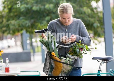 Frau lehnt sich auf ihr Fahrrad und SMS auf dem Handy Stockbild