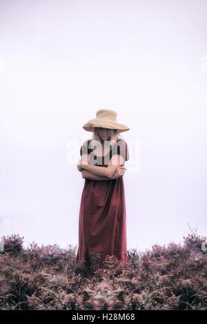 eine Frau in einem roten Kleid steht in die Heide Stockbild