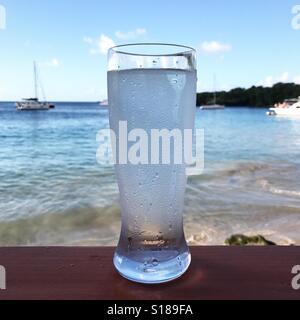 Glas Wasser mit Blick auf den Ozean Stockbild