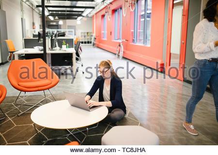 Kreative Geschäftsfrau mit Kopfhörern mit Laptop im Coworking Space Stockbild
