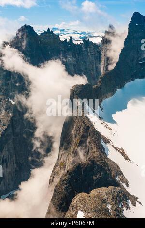 Luftaufnahme über Berge im Tal Romsdalen, Møre og Romsdal, Norwegen. Die 3000 Meter vertikale Trollmauer ist teilweise im Nebel. Stockbild