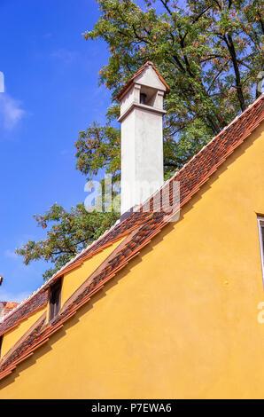 Augsburg, Bayern, Deutschland - 10. September 2015: Blick auf typische Dach Architektur mit Kamin in der Fuggerei sozialen Wohnungsbau. Stockbild