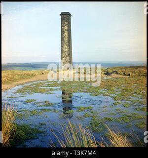 Bank Top Schornstein, Rosedale, Ryedale, North Yorkshire, 1967. Bank Top Schornstein gesehen über einen kleinen Stausee. Der Schornstein diente ein Motor Haus an der Hollins Mine (EISENSTEIN). In Rosedale in Magnetit Eisenerz 1853, eine hochwertige Eisenerz, entdeckt wurde, nur nord-östlich von Hollins Farm. Hollins war die erste von einer Reihe von Minen Rosedale gegründet werden soll, und wurde intensiv von 1859 durch die Rosedale Mining Company gearbeitet. Der Schornstein wurde 1972 abgerissen. Stockbild
