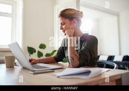 Schuss von junge Frau Büro zu Hause arbeiten. Schöne Frau mit Laptop und Dokumente am Tisch sitzen. Stockbild