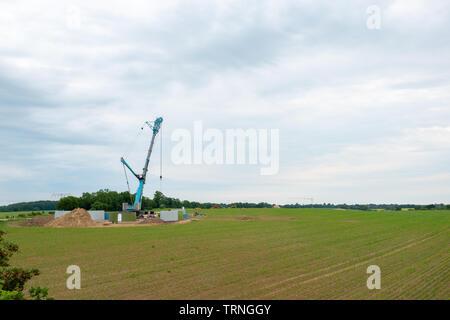 In der Mitte ein Feld, eine Windenergieanlage errichtet wird mit Hilfe von einem großen Kran Stockbild