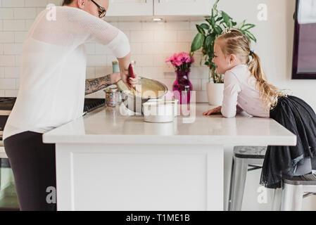 Neugierige Mädchen beobachten Mutter backen in der Küche Stockbild