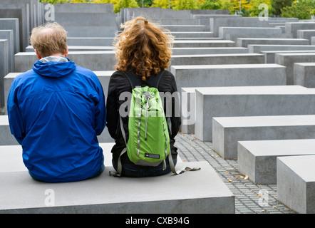 Zwei Touristen sitzen auf einem von Betonsteinen, aus denen sich das Holocaust-Mahnmal in Berlin, Deutschland Stockbild