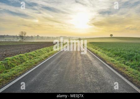 Morgensonne über eine Landstraße in Freiensteinau im Vogelsberg in Hessen, Deutschland Stockbild