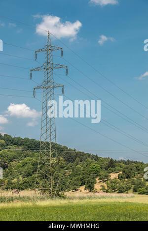 Strommast in der deutschen Landschaft mit Wäldern, Feldern und Wiesen Stockbild