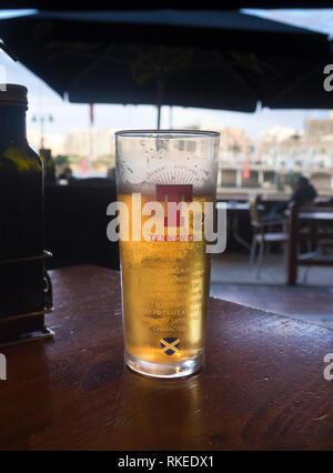 Ein Glas Tennent Bier, entspannen im Schatten an der Strandpromenade in der Nähe von Valetta, Malta Stockbild