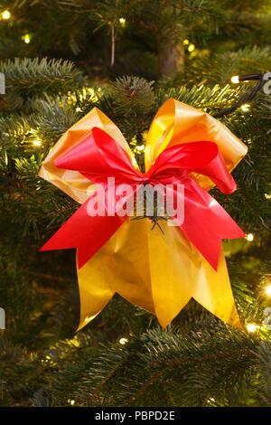 Rot-goldene Band an einem Weihnachtsbaum in der Dämmerung, Weihnachtsdekoration, Deutschland, Europa ich Rot-Goldene Schleife ein Einems Weihnachtsbaum bei Abenddämmeru Stockbild