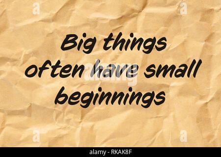 Motivierende Angebot grosse Dinge haben oft kleine Anfänge auf Zerknitterten braunen Papier gedruckt. Stockbild
