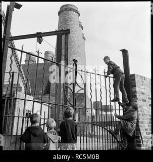 Westwood Mühlen, Lichfield Street, Hanley, Stoke-on-Trent, Staffordshire, 1965-1968. Eine Gruppe Kinder klettern Die schmiedeeisernen Tore an der Kanalseite Eingang George Goodwin und Söhne Westwood Mühlen. Stockbild