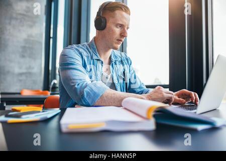 Schuss des kaukasischen Jüngling mit Kopfhörern in Bibliothek mit Laptop zu studieren. Universität Stockbild