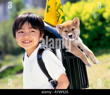 Junge mit einem Hund in seiner Schultasche Stockbild
