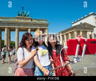 Chinesische Touristen mit selfie Stick in frontt vom Brandenburger Tor in Berlin, Deutschland Stockbild