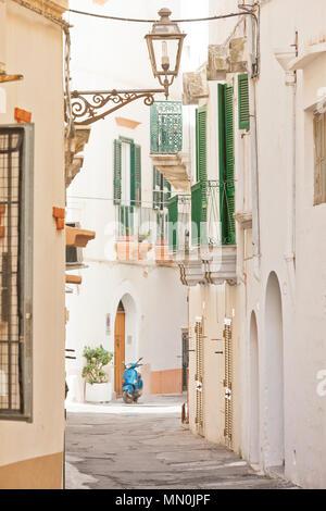 Gallipoli, Apulien, Italien - ein traditionelles Straßenlaterne in einer historischen Gasse mit einem Motorroller Stockbild