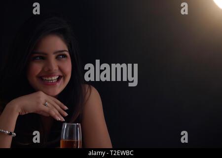 Frau mit einem Glas Wein lächelnd Stockbild