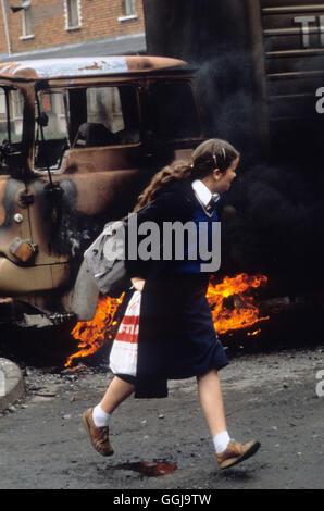 Belfast die Mühen der 1980er Jahre. Schulmädchen eilt vorbei an einem brennenden entführten LKW verwendet Stockbild