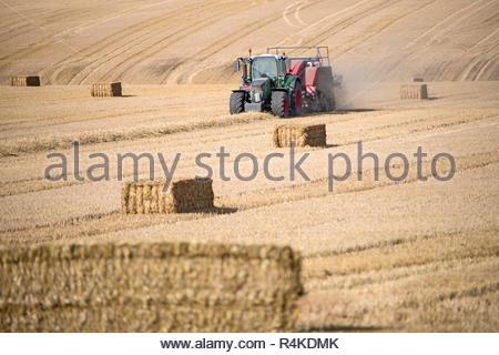 Traktor und Ballenpresse Strohballen in Feld nach dem Sommer Weizenernte auf der Farm Stockbild