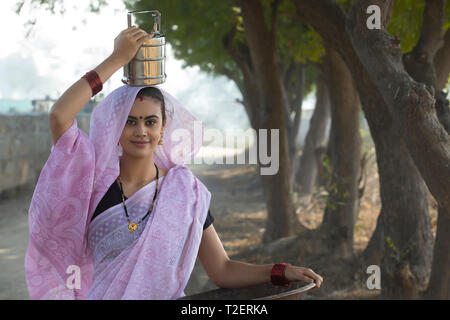 Lächelnd ländliche Frau oder tageslohn Arbeiter in Saree tragen ein Bügeleisen Gold Pan in der Hand und einem Tiffin box auf den Kopf zu arbeiten. Stockbild