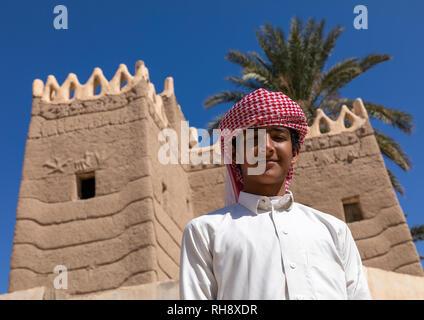 Junge saudische Mann vor einem traditionellen alten Lehmhaus, Najran Provinz Najran, Saudi-Arabien Stockbild