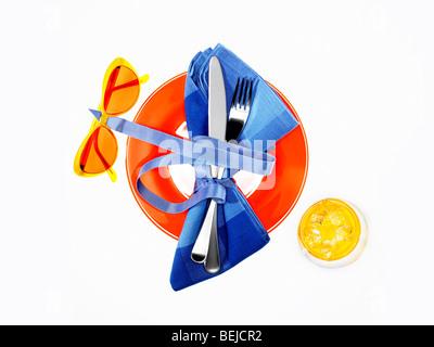 Kulinarisches Teller mit Messer und Gabel, Serviette, kaltes Getränk und Sonnenbrillen Stockbild