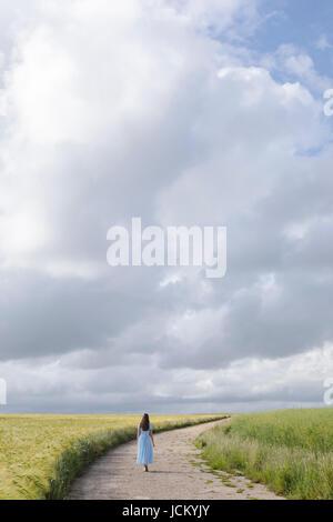 eine Frau in einem blauen Kleid ist Fuß auf einem Pfad durch Getreidefeldern Stockbild