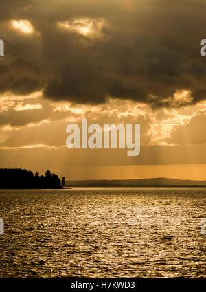 See bei Dämmerung, Silhouette des Waldes und dramatischer Himmel mit Sonnenstrahlen. Dunkle und launische Natur Stockbild