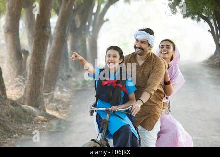 Happy ländlichen Paar zusammen mit ihrer Tochter reiten auf dem Fahrrad im Dorf. Stockbild