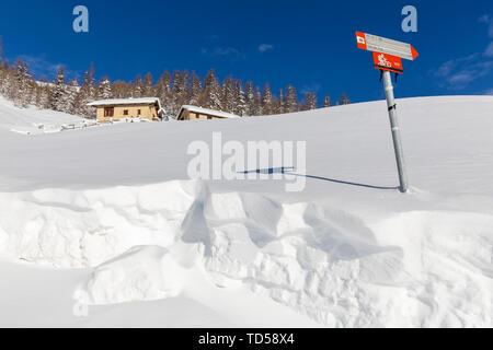 Traditionelle Hütten mit Trekking Signal im Winter, Livigno, Livigno, Lombardei, Italien, Europa Stockbild