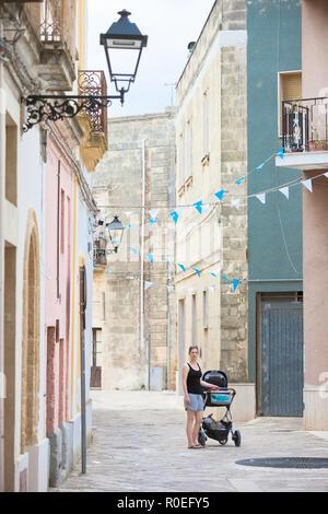 Presicce, Apulien, Italien - eine Frau, die ihre Kinderwagen durch die Altstadt Stockbild